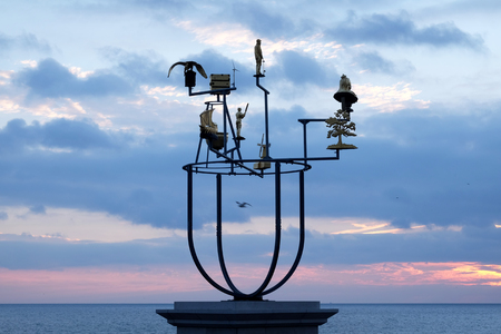 Artist's plinth on Hove seafront promenade, Brighton, UK, with a delicate metal constellation sculpture on it behind is the promenade nd the sea at sunset, the sky is red and blue from the recently set sun Banque d'images - 115590693