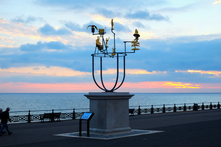 Artist's plinth on Hove seafront promenade, Brighton, UK, with a delicate metal constellation sculpture on it behind is the promenade nd the sea at sunset, the sky is red and blue from the recently set sun Banque d'images