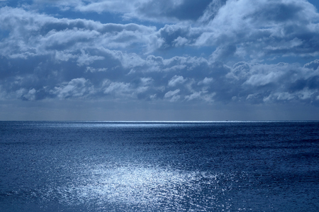 Sea and sky in the bottom half is a calm deep blue sea, on the horizon is a line of white shimmering glowing light from the moon in the upper half is the sky covered in fluffy clouds the image has a blue glow from the moonlight
