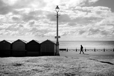 A line of four beach huts and a street lamp silhoutted black by the sun shining directly at the camera through a dramatic blue and white sky, the sea is shimmering behind the beach huts a man is sillhouetted walking towards the beach hut on the promenade, black and white photograph