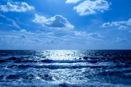 Sea and sky, in the bottom half is a deep blue sea with waves breaking, on the horizon is a line of white shimmering glowing light on the water in the upper half is the sky covered in fluffy clouds Stock Photo