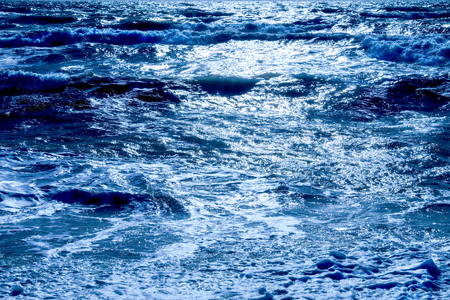 A dark blue sea with waves swelling the sea has dark shadows where the waves are swelling and the sunlight is glistening white on the sea on the horizon horizontal format