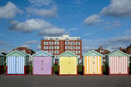 Brighton seafront five beach huts, with multi coloured doors of yellow, pink, black stripes behind is an appartment building and blue sky