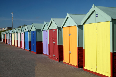 A line of 16 Beach huts with different multicoloured doors on a concrete promenade, the nearest beach huts on the right of the image are large going to very small in the distance the sky behind is blue and it is a sunny day.