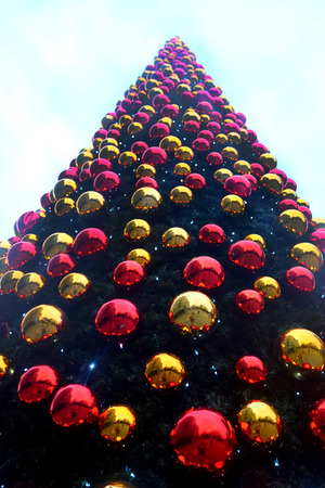 looking up from the bottom to the top of a very large christmas tree covered in hundreds of red and gold christmas baubles, vertical format 版權商用圖片