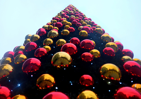 looking up from the bottom to the top of a very large christmas tree covered in hundreds of red and gold christmas baubles