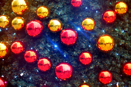 bright and chiny red and gold christmas baubles on a pine fur christmas tree