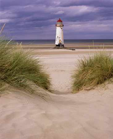 An old white light house with a bright red roof sitting on a sandy beach with a stone pathway infront, the sea is in the distance and a big blue sky with white swirling clouds is behind the light house, Talacre lighthouse, Prestatyn, North Wales, United Kingdom, UK,