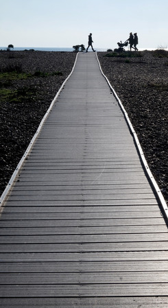 Three silhouetted unrecognisable people and a baby in a pram walking across the end of a long straight wooden pathway with a pebble beach on both sides a small line of sea and blue sky is behind