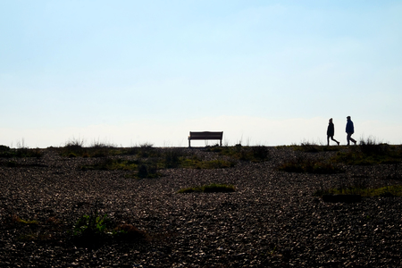 In the foreground is a pebble beach at the end of the beach are two unrecognizable people walking together as a couple they are siluoetted by the sun and sky behind, they are walking towards a park bench which is also siluoetted, Shoreham, East Sussex, UK, Stockfoto