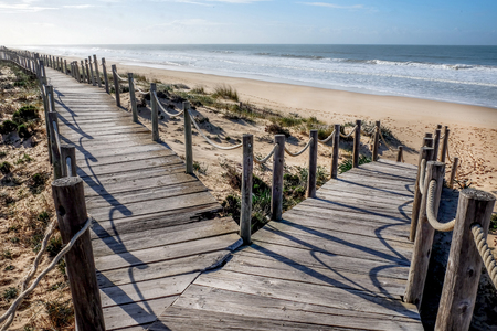 Looking down two wooden decking pathways forming a fork in the road, both heading down to a sweeping sandy beach with the blue sea and blue sky in front  Praia Da Lagoa, Algarve, Portugal. Stock Photo
