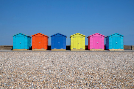 A line of six brightly coloured Beach huts, each one is a different colour in the foreground is a pebble beach and behind is a bright blue sky, Seaford, east Sussex, England, United Kingdom, UK,