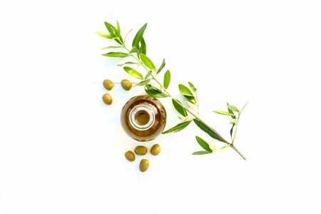 looking down on an Olive oil in a glass pouring bottle, scattered around the bottom of the bottle are seven individual olives, behind the jar is an olive branch with green leaves all are on a crisp bright white background with a lot of copy space for text