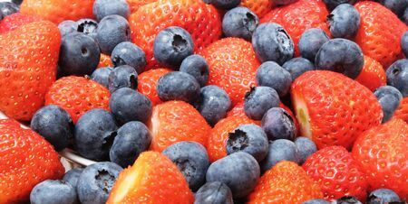 A close up of strawberries and blueberries mixed together