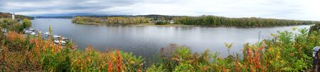 Panorama of the Hudson River in the fall. The river is curved infront are autumn trees on the left are pleasure boats moored and an island in the middle filled with autumn coloured trees. Hudson, New York state, USA