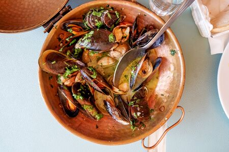 a restaurant copper serving bowl full of mussels and clams cooked in white wine sauce with garlic and parsley a traditional Portuguese dish called Ameijoas a Bulhao, Vilamoura, Algarve, Portugal