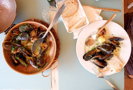 a restaurant table with a copper serving bowl and white plate full of mussels and clams, garlic and parsley a traditional Portuguese dish called Ameijoas a Bulhao, Vilamoura, Algarve, Portugal