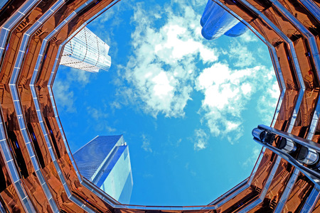 New York - October 10, 2019: The Vessel, looking up from the centre, the circular shape of the elaborate honeycomb like structure rises 16 stories, 154 flights of stairs and 2,500 steps and 80 landings for visitors to climb, in Hudson's Yard, Manhatten.