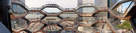 New York - October 10, 2019: The Vessel, wide panorama view of the shapes of the elaborate honeycomb like structure rises 16 stories, 154 flights of stairs and 2,500 steps and 80 landings for visitors to climb, in Hudson's Yard, Manhatten.