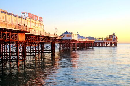 the full length of Brighton pier, the pier has an orange glow from the sun setting, the mane of the pier is on the left and the fairground is at the end the sea and sky are both calm and clear, Brighton, England, UK, Britian.