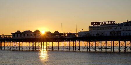 Brighton Palace pier, the front of the pier with the name on it, looking from sea, the sun is setting under the pier forming a beautiful star burst effect of orange light, the metal structure of the pier is visible and glowing orange on a calm sea