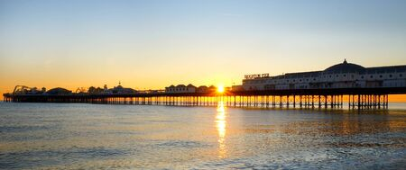 Brighton pier stretching out to sea at sunset, the front of the pier with the name on it, the sun is setting under the pier forming a beautiful star burst effect of orange light, the metal structure of the pier is visible and glowing orange on a calm sea