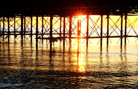 The metal support posts of Brighton pier rising out of ocean, the sun is setting under the pier forming a beautiful star burst effect of orange light, the metal post form graphical shapes glowing orange on a calm sea