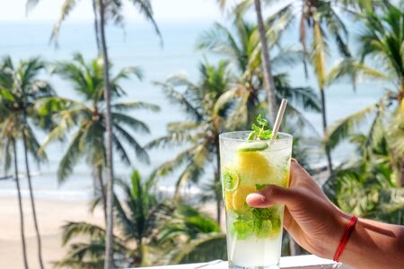 A young Asian man's hand holding a virgin mojito cocktail brightly shining in the sunshine, behind is a tropical scene of palm trees, a sandy beach and blue sea, Vagator beach, Goa, India, copy space on the left
