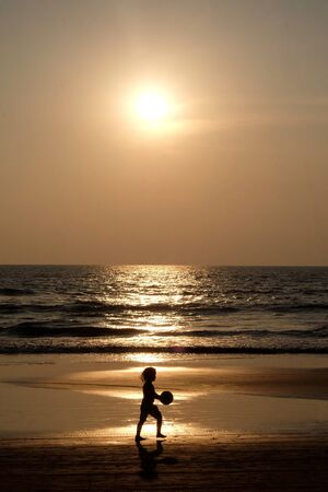 Silhouette of an unrecognizable small child holding a football walking along an empty golden sandy beach at sunset, a calm sea and clear golden sun lit sky  免版税图像
