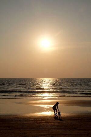 Silhouette of an unrecognizable small child picking up a football walking along an empty golden sandy beach at sunset, a calm sea and clear golden sun lit sky
