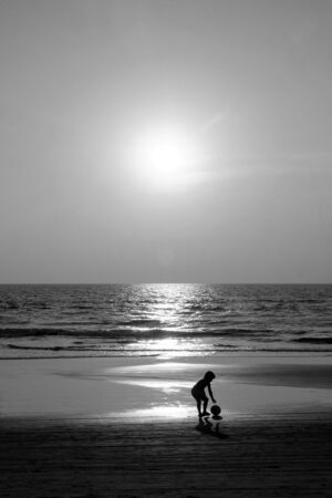 Silhouette of an unrecognizable small child holding a football walking along an empty golden sandy beach at sunset, a calm sea and clear golden sun lit sky, black and white photograph