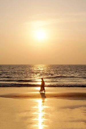 Silhouette of an unrecognizable woman wearing a traditional indian saris walking along an empty golden sandy beach at sunset, a calm sea and clear golden sun lit sky