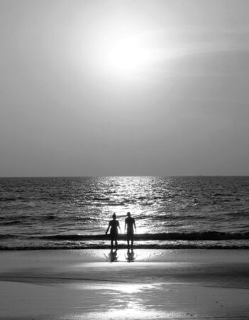 Black and White Silhouette of an unrecognizable young couple standing together on an empty golden sandy beach looking at the sunset, a calm sea and clear golden sun lit sky