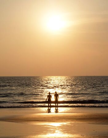 Silhouette of an unrecognizable young couple standing together on an empty golden sandy beach looking at the sunset, a calm sea and clear golden sun lit sky
