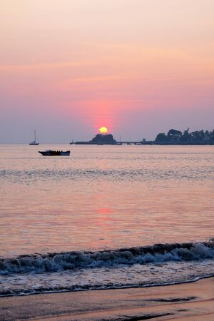 A pink glow from the sun setting over a calm sea, a speed boat is floating in the pink sea, Dona Paula Bay, Panjim, Goa