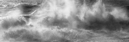 A line of white spray capturing the dramatic moment a wave breaks in a rough stormy sea sending white spray and waves high in to the air, motion and blur