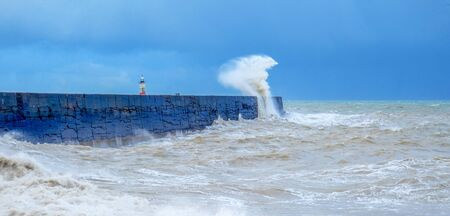 A harbor wall with a rough stormy sea crashing against the wall causing the sea to be blurred and in motion, behind is a red and white lighthouse, waves are crashing over the wall, there is a blue sky behind 免版税图像