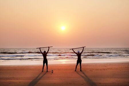 two unrecognizable men exercising at sunset by holding two wooden poles as weights on a wide open empty sandy beach, they are standing with their arms outstretched, holding the poles, they are lined up looking at the sun setting directly infront of them, there is a red and orange glow in the sky and reflected on the sea, lots of text space in the image