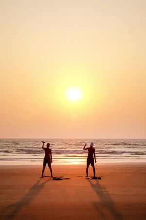 two unrecognizable men exercising at sunset by holding two small weights on a wide open empty sandy beach, they are standing with their arms outstretched, holding the poles, they are lined up looking at the sun setting directly infront of them, there is a red and orange glow in the sky and reflected on the sea, lots of text space in the image 免版税图像
