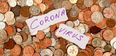 The words corona virus written in purple ink on two pieces of ripped white paper laying on top of hundreds of silver and copper coloured coins, pound sterling British currency