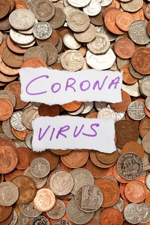 The words corona virus written in purple ink on two pieces of ripped white paper laying on top of hundreds of silver and copper coloured coins, pound sterling British currency, vertical format 免版税图像
