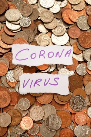 The words corona virus written in purple ink on two pieces of ripped white paper laying on top of hundreds of silver and copper coloured coins, pound sterling British currency, symbolising corona virus crisis and money
