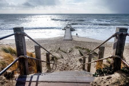Weathered wooden steps leading down onto a sandy beach leading to the wide open sea with a wooden jetty leading to a small rock island, a silhouette of the distant figure of a man exercising on the beach, Southbourne Beach, Christchurch, Dorset, England, United Kingdom
