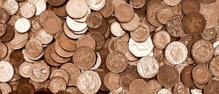 UK currency, hundreds of British copper and silver colored coins randomly piled ontop of each other, one pound coins, fifty pence, twenty pence, two pence, one pence,   免版税图像