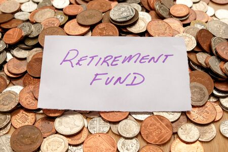 The words retirement fund written in purple pen on white paper, the paper is on top of hundreds of silver and copper coloured British coins