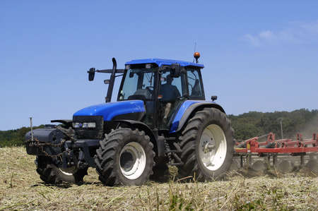 the harvest of colza with machines like a reaping-machine threshing-machine and tractor photo