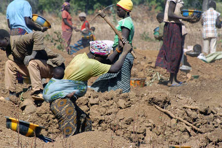 To the goldmine of Poura the gold diggers come from everywhere in the hope of finding a little gold after the season of the cultures. Women, children and men of very old are here in a universe of dust under a blazing sun. In Burkina Faso Faso the research Stock Photo - 11556273