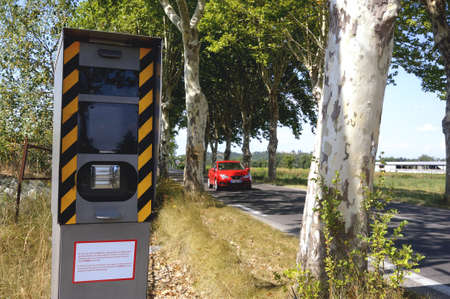 Radar on a French road hidden behind an alignment of trees. Stock fotó - 17697542