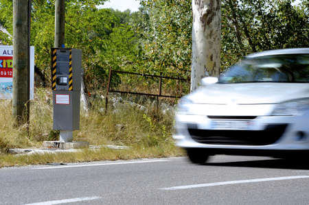 Radar on a French road hidden behind an alignment of trees. Stock Photo