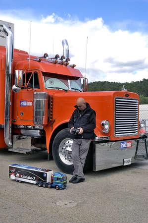 truck driver: lorry driver having fun with a small truck radiocontrolled in front of its enormous truck Editorial